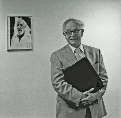John Ward poses in 1985 with the photo of Charles Seeger marking the entrance to the Charles Seeger Room at the Loeb Music Library.