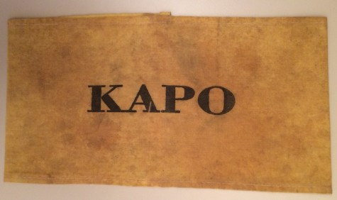 "An armband stamped with the word ""KAPO,"" designating a concentration camp enforcer drawn from the camp population itself."