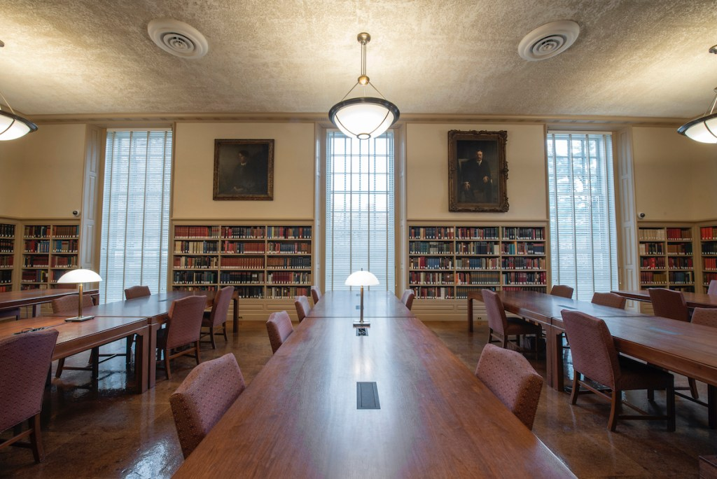 An image of Houghton's reading room, displaying three chandeliers, bookshelf-lined walls, three windows, three rows of tables, and two portraits.