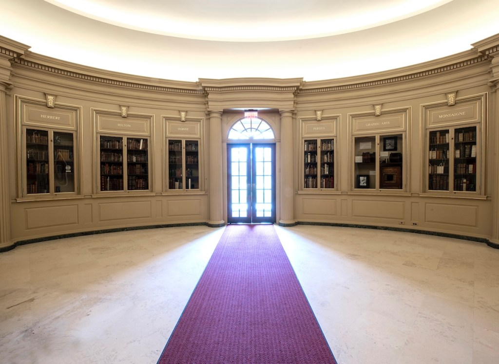 Light streams into the Houghton Library lobby through the front door, which is flanked by six glass-panelled bookcases.