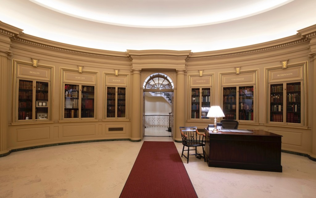 Houghton Library's lobby ca. 2018–2019, featuring six glass-panelled bookcases, a desk with chair and lamp, and a carpet runner that leads to a spiral staircase behind an arched doorway.