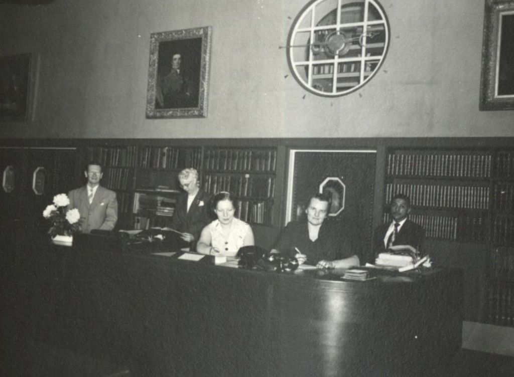 Five people stand behind a library reading room service desk.