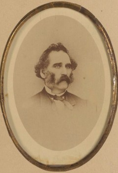 Man in suit and tie with large muttonchop sideburns and full mustache.