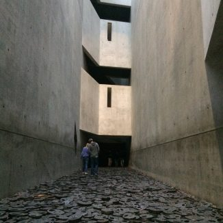 This art exhibit in the Jewish Museum is eery. The towering bare cement walls remind one of a prison cell... or a grave vault. The mouths of the iron faces are open, as if crying out, and they clank like chains as visitors step on them.