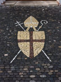 This mosaic, depicting a bishop's mitre, cross, and shepherd staff, is on the sidewalk outside the old bishop's apartment on the main square.