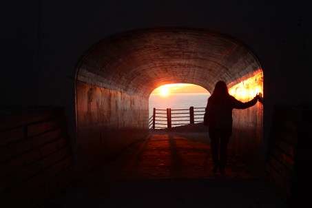 girl walking through a tunnel towards the sunset