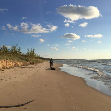 Lake Michigan beach and girl climbing on washed up driftwood.