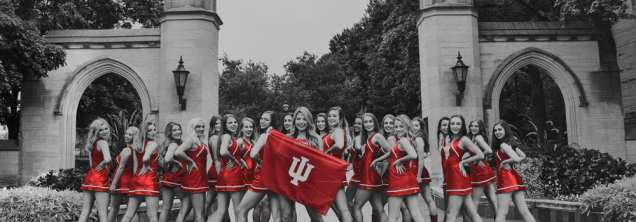 dance team in red uniforms with IU flag, outside at Sample Gates