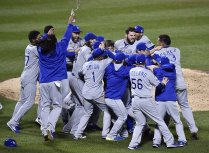The Kansas City Royals rush to relief pitcher Wade Davis to celebrate after defeating the New York Met 7-2 to win the World Series on Sunday, November 1, 2015 at Citi Field in New York. Photo courtesy of Jill Toyoshiba, Kansas City Star, jtoyoshiba@kcstar.com
