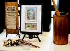 """Artifacts from 19th century United States were displayed on a table. Left: posters advertising the sale of slaves and other items were common during the period. Middle: a bill from North Carolina featured a slave picking cotton. Underneath, a piece of cotton lies on the table. Right: a large, wooden mortar and pestle was one of the tools brought over from Africa to the United States. It was used for """"polishing the rice"""", a term used to describe separating the rice kernels from their husks. They were also used for grinding corn meal, making wheat flour, and making peanut butter. Photo by Andrew Hartnett."""