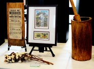 "Artifacts from 19th century United States were displayed on a table. Left: posters advertising the sale of slaves and other items were common during the period. Middle: a bill from North Carolina featured a slave picking cotton. Underneath, a piece of cotton lies on the table. Right: a large, wooden mortar and pestle was one of the tools brought over from Africa to the United States. It was used for ""polishing the rice"", a term used to describe separating the rice kernels from their husks. They were also used for grinding corn meal, making wheat flour, and making peanut butter. Photo by Andrew Hartnett."