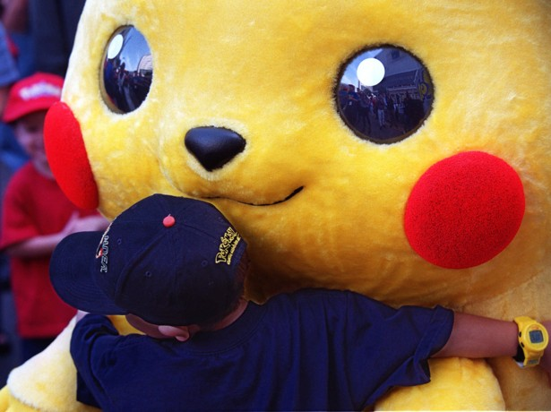 """Daniel Osugi, 7, of Long Beach, Calif., hugs an oversized Pokemon character known as """"Pikachu"""" at the premiere of the new Warner Bros. animated feature, """"Pokemon The First Movie,"""" Saturday, Nov. 6, 1999, at the Mann's Chinese Theatre in the Hollywood section of Los Angeles.  Pikachu is the main character of the animated adventure, based on the hit Japanese TV series and video game.  (AP Photo/Chris Pizzello)"""