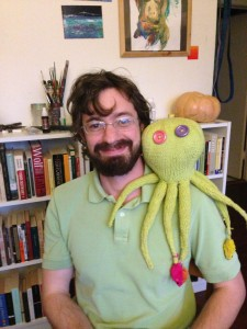 Photo of Jonathan Gingerich wearing a green shirt with a green knit octopus sitting on his shoulder