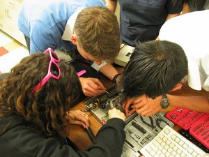 three students hacking on the inside of small box on the ground, at the same time