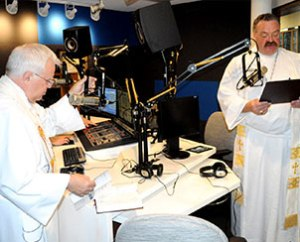 KFUO Director of Broadcast Services Rev. Rodney Zwonitzer, left, and LCMS President Rev. Dr. Matthew C. Harrison offer prayers and thanks during the June 24 dedication and blessing of the new KFUO studios at the LCMS International Center in St. Louis. (KFUO/Gary Duncan)