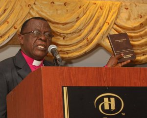 The Rt. Rev. Dr. Paul Kofi Fynn, president of the Evangelical Lutheran Church of Ghana, holds a copy of the newly published Komba New Testament as he addresses some 200-plus guests at the first Lutheran Bible Translators (LBT) 50th anniversary dinner May 2 in Lisle, Ill. The Komba translation is one of 39 completed by LBT in 18 countries. (Lutheran Bible Translators/Kellwood Studio Photography)
