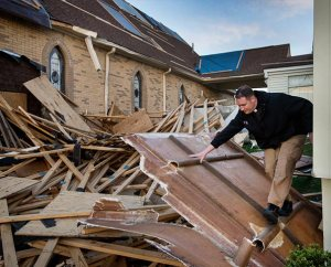 The Rev. Michael Meyer, manager of LCMS Disaster Response, climbs through debris May 1 at Holy Trinity Lutheran Church in Tupelo, Miss. The storm blew off part of the church's roof, tore off its steeple and blew out several windows. (LCMS Communications/Erik M. Lunsford)