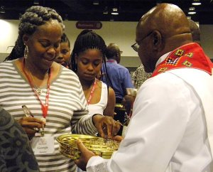 Worshipers receive Holy Communion during the July 9 opening service of the Black Ministry Family Convocation in Kansas City, Mo. More than 460 people took part in the five-day convocation, which focused on witness and outreach. (LCMS/Paula Schlueter Ross)