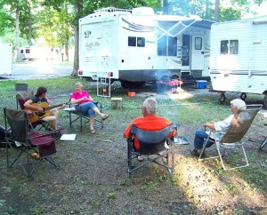 Heidi Wilkinson strums her guitar for fellow Laborers, from left, Cindy Trombley, Gary Trombley and A.J. Hunter, at the end of a day of working for Lutheran Housing Support to help Fort Wayne homeowners in need. Laborers live in their RVs, camped at a city park, during the Helping Hand project.  (Lutheran Church Extension Fund)
