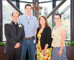 The Rev. Dan McMiller, left, poses with coworkers, from left, David Fiala, Maureen Williams and Erin Alter after his installation as director of recruitment for the LCMS Office of International Mission. (LCMS/Erik M. Lunsford)