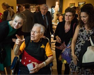 """The Rev. Otto J. Hintze, commissioned as the first LCMS missionary to New Guinea (now Papua New Guinea), browses artifacts with family, including his granddaughter, Ellie Hintze (left), during the Oct. 5 public opening of Concordia Historical Institute's """"Bringing Christ to the Highlands"""" exhibit. (LCMS/Erik M. Lunsford)"""