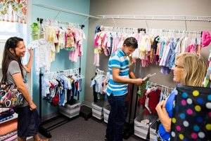 "From left, Sweet Rose and Arnie Suan chat with Barb Erickson in the boutique of donated baby clothes and supplies during an Aug. 15 tour of the newly-opened Iowa Life Care Clinic in Creston, Iowa. The clinic opened out of a former Planned Parenthood facility once known for its controversial ""telemedicine"" abortions. (LCMS/Erik M. Lunsford)"