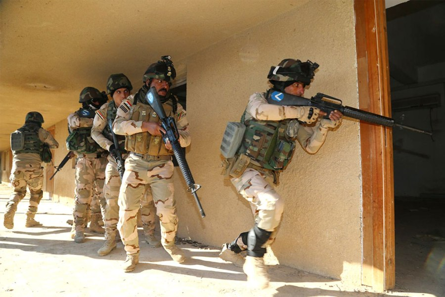 Iraqi soldiers enter a room after breaching the doorway to ensure that it is clear at Camp Taji training Jan. 10 in Iraq. The training is part of a multinational effort to train Iraqi security forces to defeat the Islamic State of Iraq and the Levant. (Army photo by Sgt. Kalie Jones)