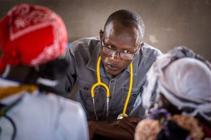 A Kenyan doctor who assisted the MMT examines patients during the clinic.