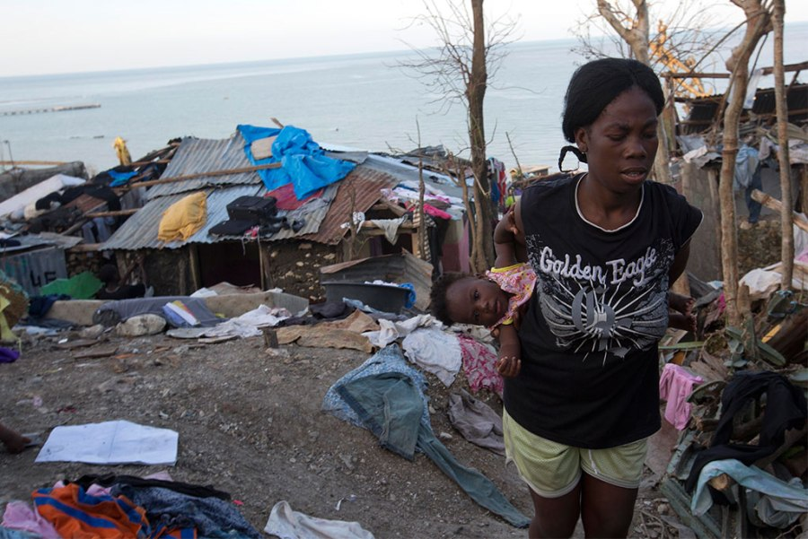 On Oct. 7, a woman carries her daughter as she walks through wreckage caused by Hurricane Matthew in Jeremie, Haiti. (AP Photo/Dieu Nalio Chery)