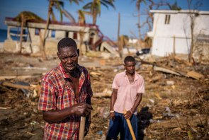 Haitian men work to clear the debris left by the hurricane's severe winds that reportedly reached 140 miles per hour.