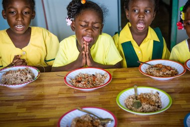 Primary-school students pray before eating a free lunch provided through the Belize Mission Society's meals program.