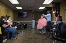 The Rev. Micah Glenn, new national missionary to Ferguson, chats with old friends during a haircut on Wednesday, April 20, 2016, near Ferguson, Mo.