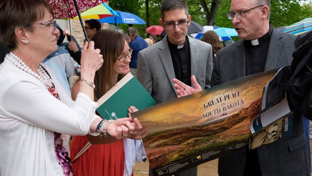 "Joshua Vogel, center, and his wife, Pamela, learn about Joshua's vicarage assignment to Concordia Lutheran Church in Cresbard, S.D., from LCMS South Dakota District President Rev. Scott Sailer, right, on ""Call Day"" (April 26) at Concordia Seminary, St. Louis. Holding the umbrella is Sailer's wife, Sarah. The LCMS Council of Presidents placed 116 pastoral candidates and assigned 85 vicars throughout the Synod when it met April 22-25 in Fort Wayne, Ind. (Sid Hastings/Concordia Seminary, St. Louis)"