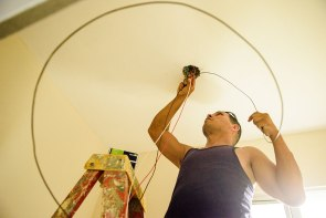 Mauricio Guedez lassos an electrical cord around his hand as he finishes electrical work in the building.
