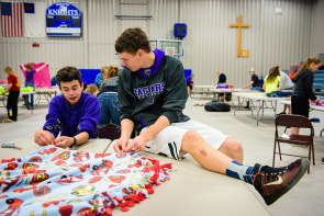 Students chat while making blankets and assembling Christian care kits at Martin Luther High School in Northrop, Minn.