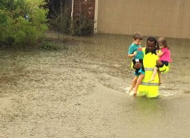 Deputy Rick Johnson of the Harris County Sheriff's Office carries Joel, 4, and Skylar, 2, through floodwaters outside their home in Cypress, Texas, Aug. 27. The photo — shown repeatedly on national news and morning TV shows — went viral when numerous Facebook and Twitter users also shared it as a symbol of racial harmony. (Harris County Sheriff's Office)