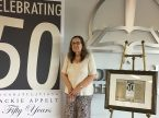 Senior Designer Jackie Appelt poses with a congratulatory banner and her 50th anniversary gift at Concordia Publishing House in St. Louis. Appelt says she has no plans to retire from the position, one she believes God led her to. (Concordia Publishing House/Tim Agnew)
