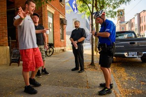 Suguitan listens as a bystander describes to a Cincinnati police officer the man who stabbed a homeless person a block from the church.
