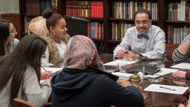 "The Rev. Dr. John A. Nunes, right, president of Concordia College—New York in Bronxville, N.Y., talks with students during a class. This fall the school — which touts ""radical hospitality"" and a ""student-first mentality"" — saw a 35-percent increase in enrollment. (Concordia College—New York)"