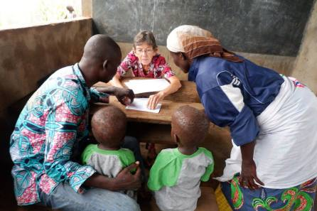 Missionary Valerie Stonebreaker helps a family with intake.