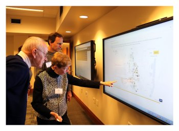 Betty Nelson, dean of students emerita, and her husband, Dick, professor emeritus of educational studies, explore the new historic building database as computer science professor Chris Clifton looks on.