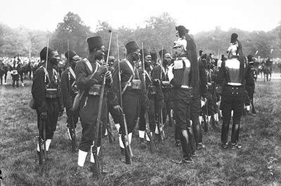 Un cuirassier français en armure s'adresse à des tirailleurs sénégalais lors du défilé du 14 juillet 1913