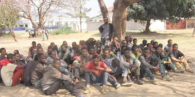 Ethiopian migrants who were arrested by the police, await trial outside the Karonga Court in Malawi, in September 2014. Photo credit: Tiwonge Kumwenda, VOA