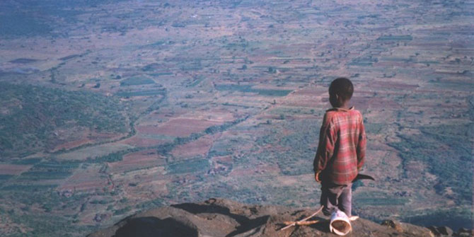 Young boy stand on mountain looking at land below