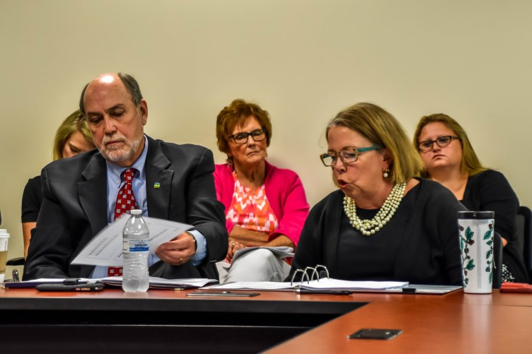 Speakers speak and handle paperwork at a council meeting