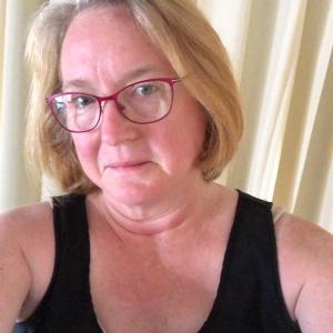 Sharon looks confidently at her audience with shoulder length hair and glasses