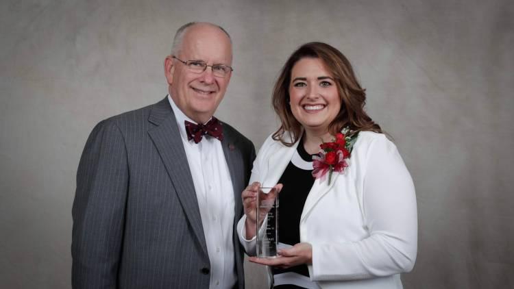 Jody Glazner holding award with President Smart