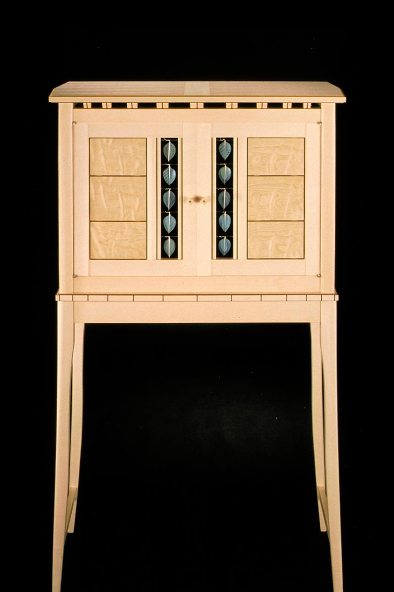 Front-view of wood furniture piece with enameled metal accents