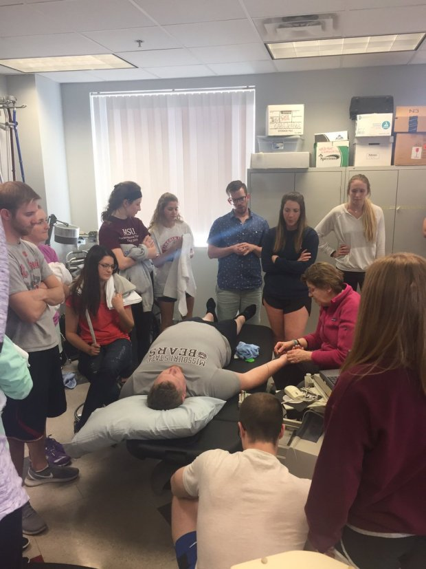 Students watching faculty instruction with patient
