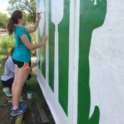 student paints sign at fairbanks